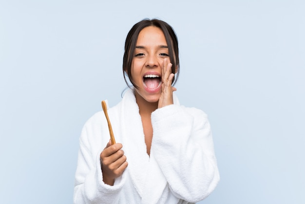 Młoda brunetki kobieta szczotkuje zęby nad odosobnioną błękit ścianą krzyczy z usta szeroko otwarty w szlafroku