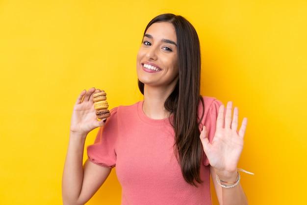 Młoda brunetki kobieta trzyma kolorowych francuskich macarons i salutuje