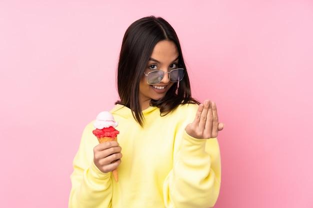 Młoda brunetki kobieta trzyma kornet lody nad odosobnioną menchii ścianą zaprasza przychodzić z ręką. cieszę się, że przyszedłeś