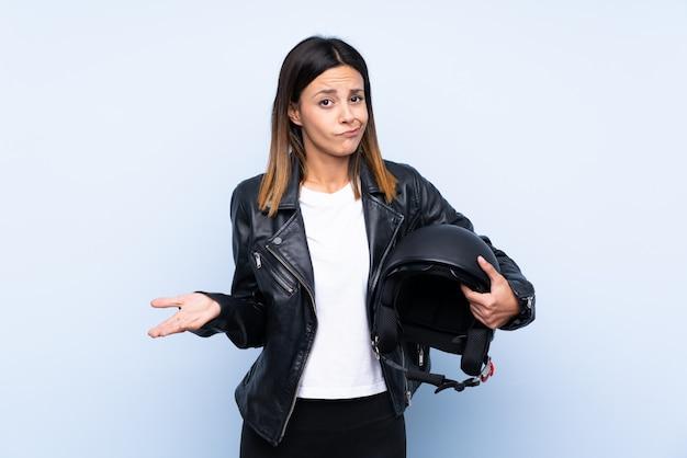 Młoda brunetki kobieta trzyma motocyklu hełm nad błękit ścianą robi wątpliwość gestowi podczas gdy podnoszący ramiona