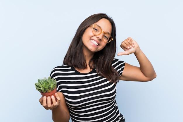 Młoda brunetki kobieta trzyma rośliny dumnej i jaźni satysfakcjonującej