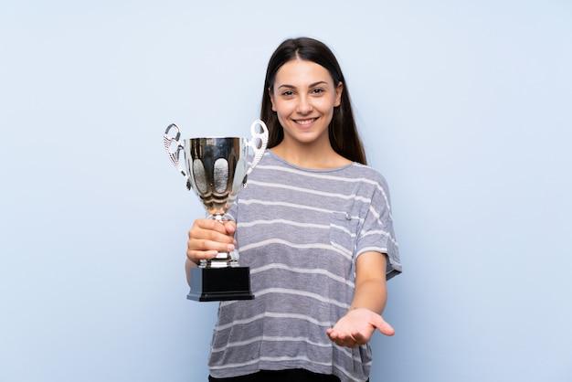 Młoda brunetki kobieta trzyma trofeum nad odosobnioną błękit ścianą