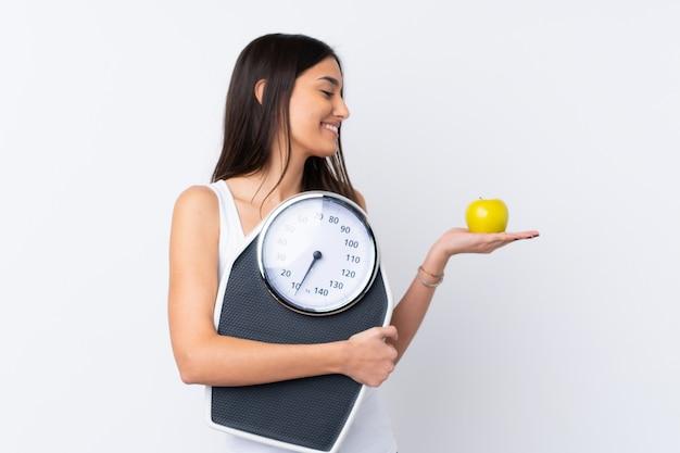 Młoda brunetki kobieta trzyma ważącą maszynę nad odosobnioną biel ścianą podczas gdy patrzejący jabłka
