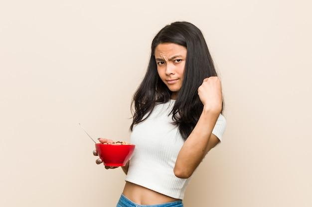 Młoda brunetki kobieta trzyma zboże puchar i pokazuje pięść
