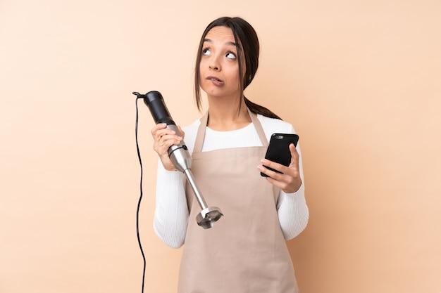 Młoda brunetki kobieta używa ręka blender nad odosobnioną ścienną mienie kawą brać daleko od i wiszącą ozdobą podczas gdy myśleć coś