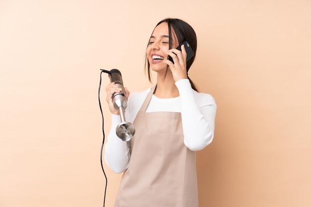 Młoda brunetki kobieta używa ręka blender nad odosobnioną ścienną mienie kawą brać daleko od i wiszącą ozdobą