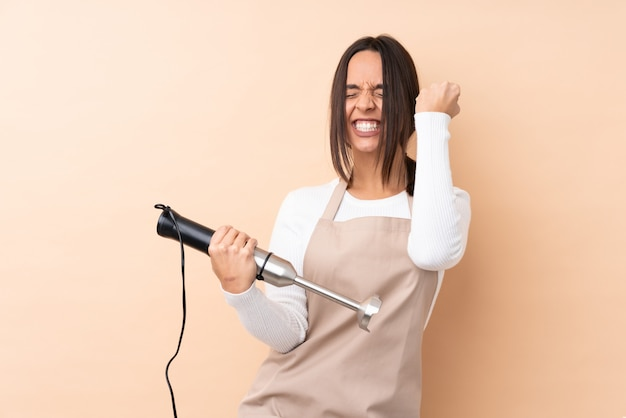 Młoda brunetki kobieta używa ręki blender świętuje zwycięstwo nad odosobnioną ścianą