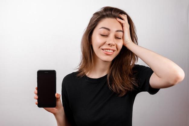 Młoda brunetki kobieta w czarny koszulki ono uśmiecha się pokazuje telefon na bielu