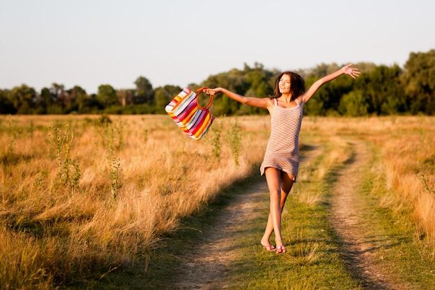 Młoda brunetki kobieta w mini sukni z torby doskakiwaniem na wiejskiej drodze i czuć szczęśliwy w letnim dniu