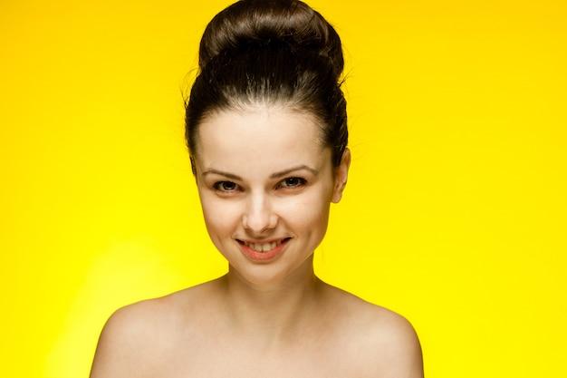 Młoda brunetki kobieta w żółtych szkłach, portret na żółtej ścianie