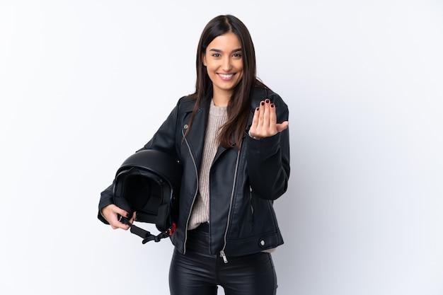 Młoda brunetki kobieta z hełma motocyklu nad odosobnioną biel ścianą zaprasza przychodzić z ręką. cieszę się, że przyszedłeś