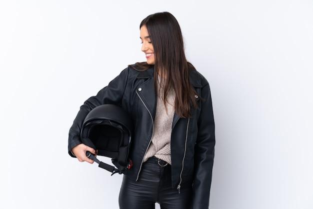 Młoda brunetki kobieta z motocyklu hełmem nad odosobnioną biel ścianą z szczęśliwym wyrażeniem