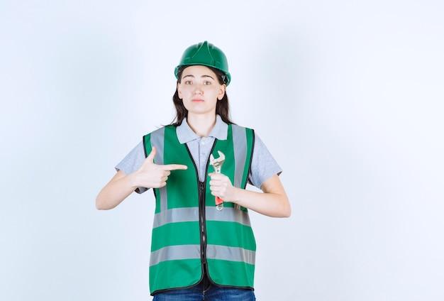 Młoda brygadzistka robi znak ręką trzymając młotek przed szarej ściany