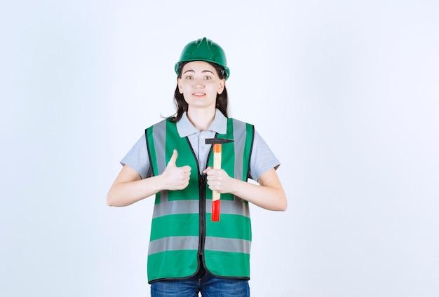 Młoda brygadzistka robi znak ręką trzymając młotek