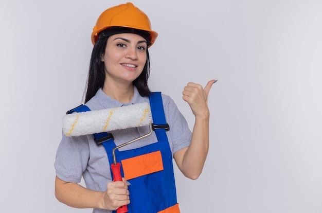 Młoda budowniczka w mundurze budowlanym i kasku ochronnym trzymająca wałek do malowania patrząc z przodu uśmiechnięta wesoło, wskazująca palcem wskazującym na bok, stojąca nad białą ścianą