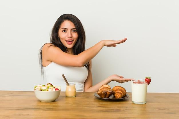 Młoda bujna kobieta bierze śniadanie szokuje i zadziwia trzymający odbitkową przestrzeń między rękami.