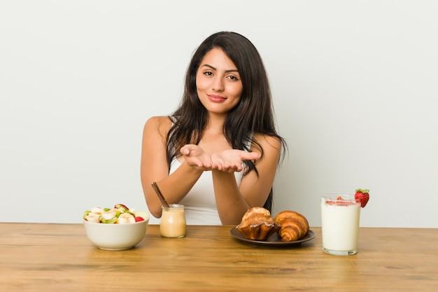 Młoda bujna kobieta bierze śniadaniowego mienie coś z palmami, oferuje kamera.