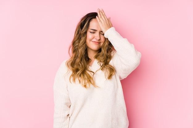 Młoda bujna kobieta pozuje w różowej ścianie odizolowywał zapominając coś, uderzając czoło dłonią i zamykając oczy.