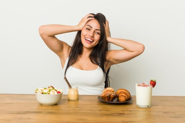 Młoda bujna kobieta przy śniadaniu śmieje się z radością trzymając ręce na głowie. koncepcja szczęścia.