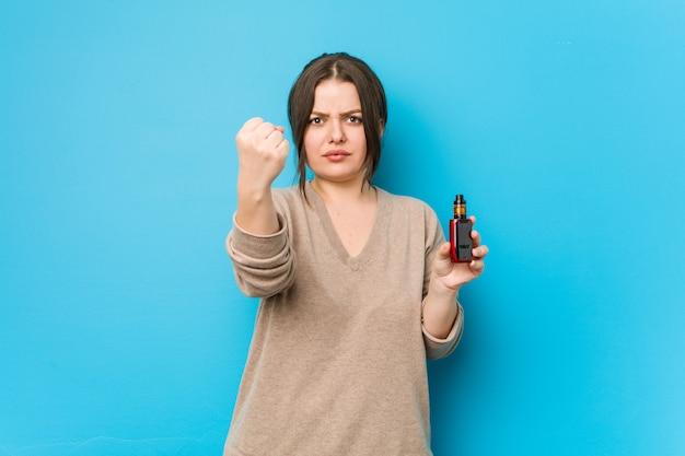 Młoda bujna kobieta trzyma odparowalnik pokazuje pięść kamera, agresywny wyraz twarzy.