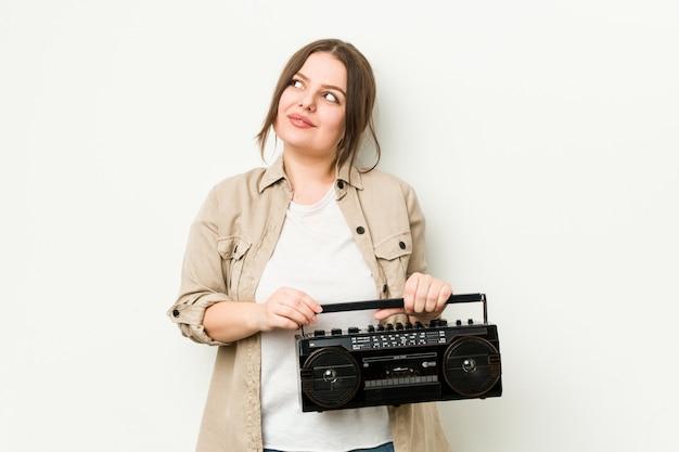 Młoda bujna kobieta trzyma retro radio marzy o osiąganiu celów i zamierzeń