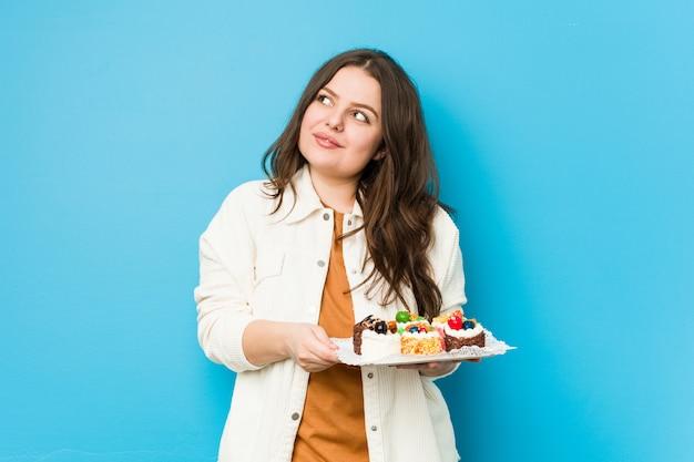 Młoda bujna kobieta trzyma słodkie torty marzy o osiągnięciu celów
