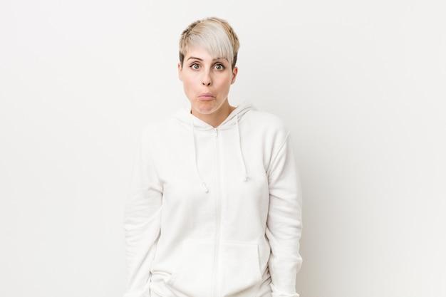 Młoda bujna kobieta ubrana w białą bluzę z kapturem wzrusza ramionami i ma otwarte oczy.