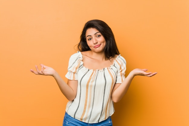 Młoda bujna kobieta wątpi i wzrusza ramionami w pytającym geście.