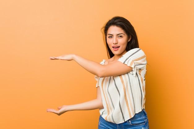 Młoda bujna kobieta zszokowana i zdziwiona, trzymając kopię miejsca między rękami.