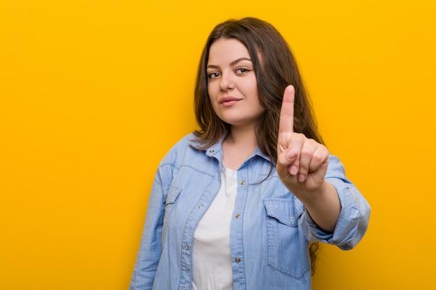 Młoda bujna plus size kobieta pokazuje numer jeden z palcem.