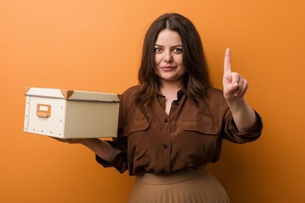 Młoda bujna plus size kobieta trzyma pudełko pokazuje liczbę jeden z palcem.