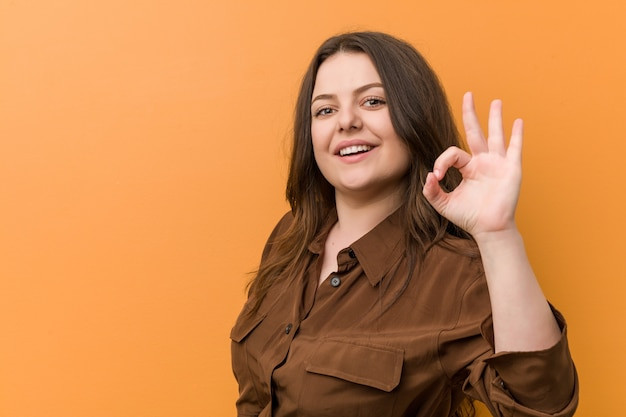 Młoda bujna rosyjska kobieta rozochocona i ufna pokazuje ok gest.