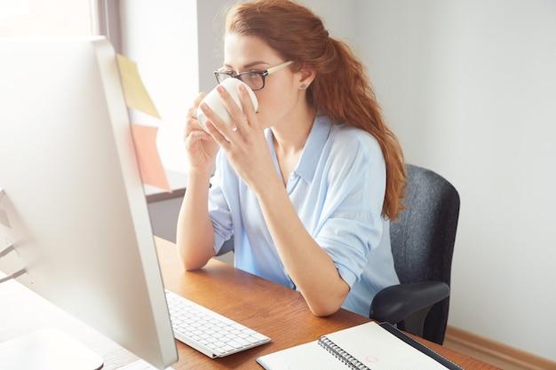 Młoda businesswoman czyta coś na komputerze przy kawie