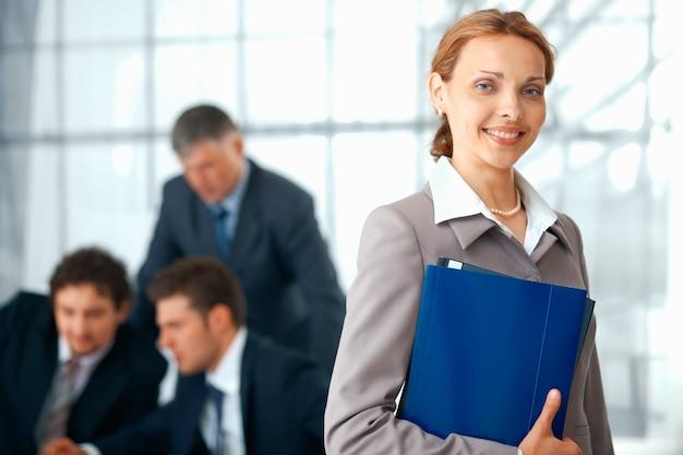 Młoda businesswoman gospodarstwa niebieski folder z kolegami pracującymi w tle.