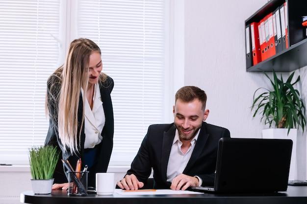 Młoda businesswoman rozmowy z kolegą na biurko z uśmiechem