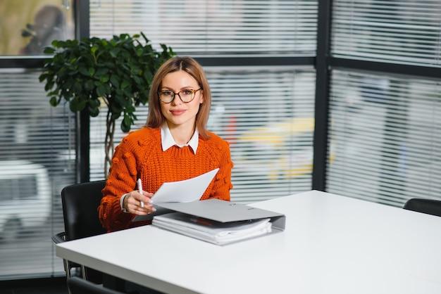 Młoda businesswoman siedzi w miejscu pracy i czyta papier w biurze