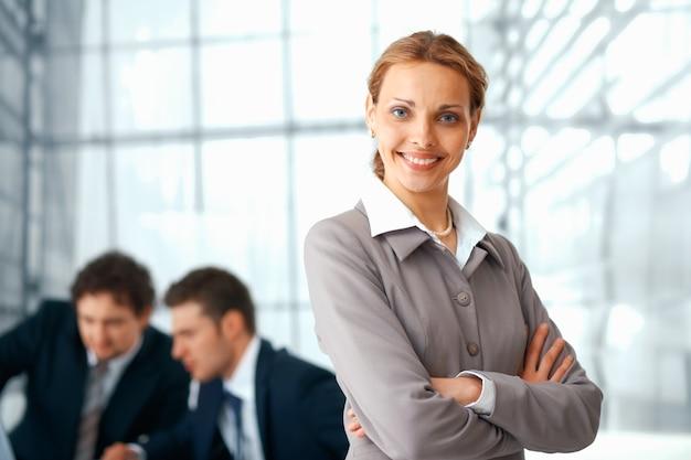 Młoda businesswoman stojącej z założonymi rękami, jej koledzy w tle.