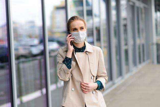 Młoda businesswoman ubrana w maskę zdrowia i rozmawiająca przez telefon w mieście