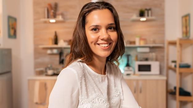 Młoda businesswoman uśmiecha się do kamery późno w nocy pracuje nad projektem. skoncentrowany przedsiębiorca w domowej kuchni korzystający z notebooka w późnych godzinach wieczornych.
