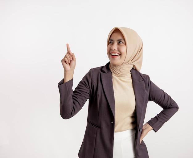 Młoda businesswoman uśmiechnięta wskazując miejsce na kopię, koncepcja pracy biurowej na białym tle