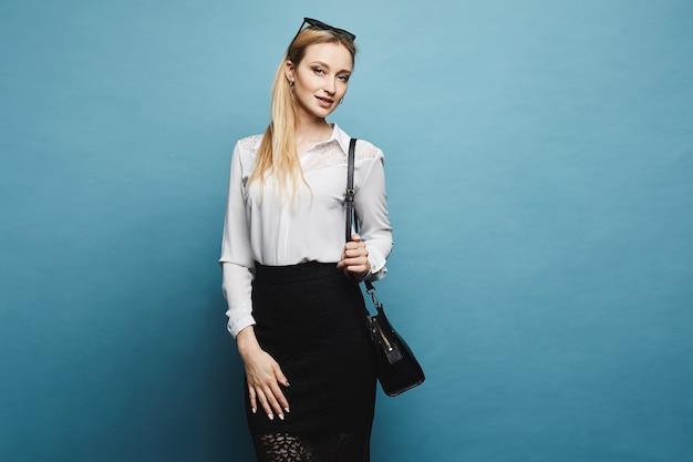 Młoda businesswoman w białą bluzkę i czarną spódnicę patrząc w kamerę i stwarzających na niebieskim tle, odizolowane