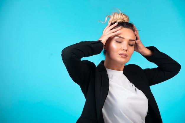 Młoda businesswoman w kok na sobie czarną marynarkę, trzymając głowę.