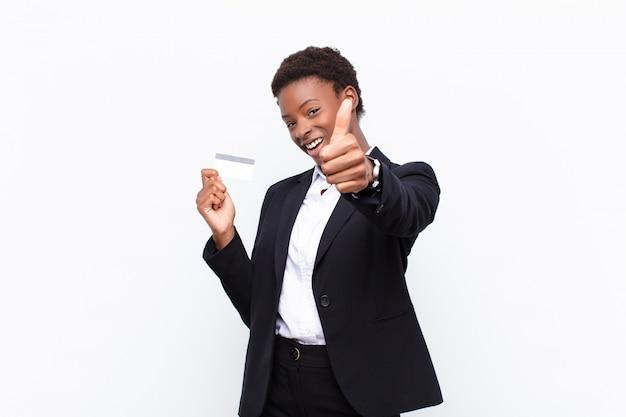 Młoda, całkiem czarna kobieta czuje się dumna, beztroska, pewna siebie i szczęśliwa, uśmiechając się pozytywnie z kciukami do góry, trzymając kartę kredytową