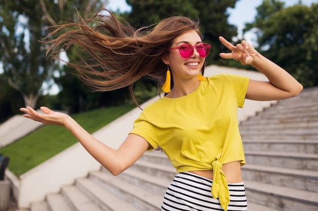 Młoda, całkiem stylowa uśmiechnięta kobieta bawiąca się w parku miejskim, pozytywna, emocjonalna, ubrana w żółty top, mini spódniczka w paski, różowe okulary przeciwsłoneczne, trend w modzie na lato, długie włosy, pokazujący znak pokoju