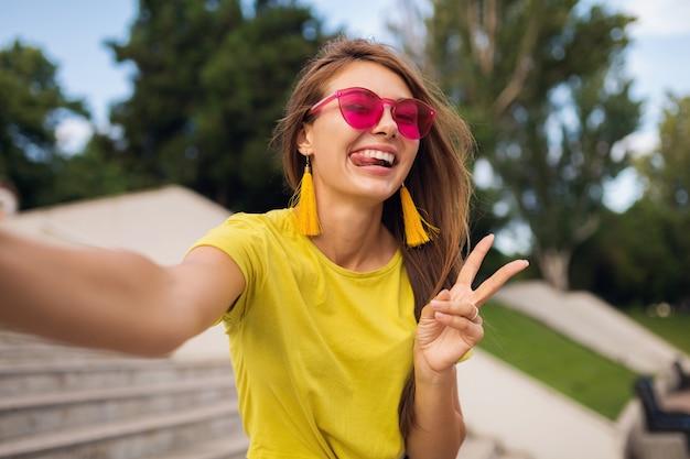 Młoda, całkiem stylowa uśmiechnięta kobieta robi selfie w parku miejskim, pozytywna, emocjonalna, ubrana w żółtą górę, różowe okulary przeciwsłoneczne, trend w modzie na lato, długie włosy, pokazujący znak pokoju