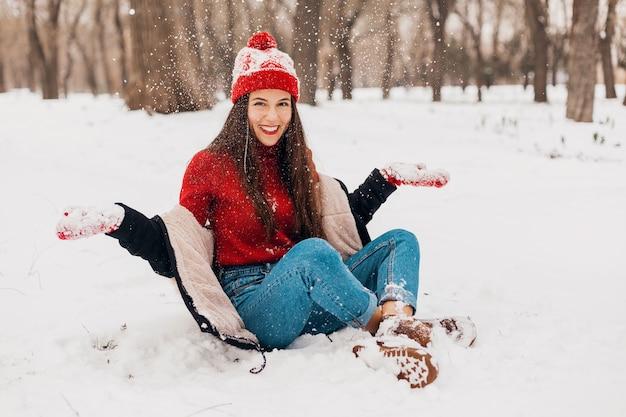 Młoda, całkiem szczera uśmiechnięta szczęśliwa kobieta w czerwonych rękawiczkach i czapce z dzianiny w czarnym płaszczu, spacery w parku w śniegu, ciepłe ubrania, zabawa