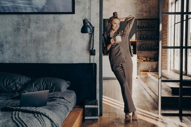 Młoda całkiem szczęśliwa kobieta ubrana w brązową satynową piżamę, trzymająca kubek z filiżanką kawy stojąc w drzwiach sypialni po przebudzeniu rano w domu, kobieta rozpoczynająca nowy dzień