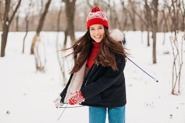 Młoda całkiem uśmiechnięta szczęśliwa kobieta w czerwonych rękawiczkach i czapce na sobie płaszcz zimowy, spacery w parku w śniegu, ciepłe ubrania