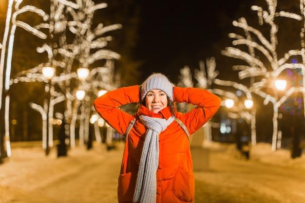 Młoda całkiem zabawna dziewczyna zabawy na świeżym powietrzu w zimie. koncepcja święta bożego narodzenia, miasta i ferii zimowych.