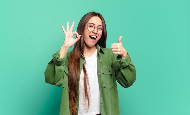 Młoda, całkiem zwyczajna kobieta czuje się szczęśliwa, zdumiona, zadowolona i zaskoczona, pokazując gesty w porządku i kciuki w górę, uśmiechając się